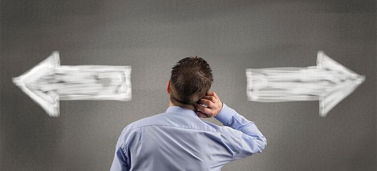 TITULO: 4 erros que você não pode cometer em seu e-commerce. Na foto aparece uma seta apontando pra lados opostos e um homem de costas coçando a cabeça como se estivesse indeciso pra qual caminho tomar