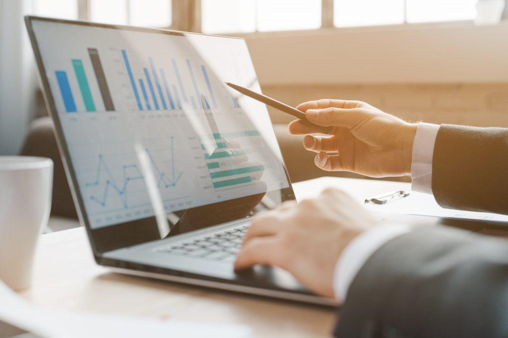 KPI'S para alavancar o seu negócio! À esquerda da imagem, sobre a mesa, um notebook que apresenta gráficos. À direita da imagem, as mãos de uma pessoa apontando para o notebook.