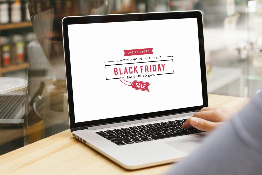 Sobre a mesa, um notebook apresentando a seguinte mensagem: Black Friday 2020. À direita da imagem, a mão de uma pessoa usando o teclado do notebook.